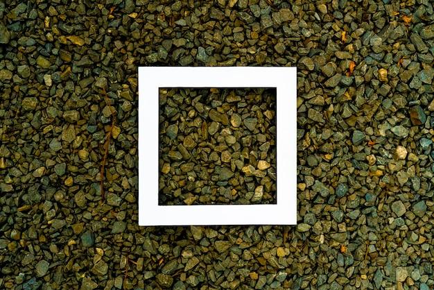 Steinhintergrundbeschaffenheit der unterschiedlichen farbe mit rahmen des weißen quadrats auf die oberseite mit exemplarplatz