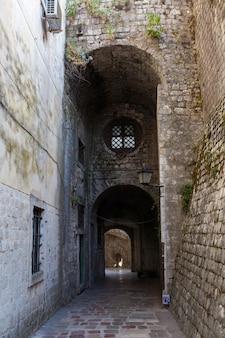 Steiniger alter korridor mit rundem fenster in der altstadt von kotor