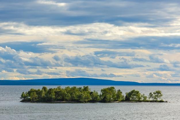 Steininsel im see mit wald bedeckt. Premium Fotos
