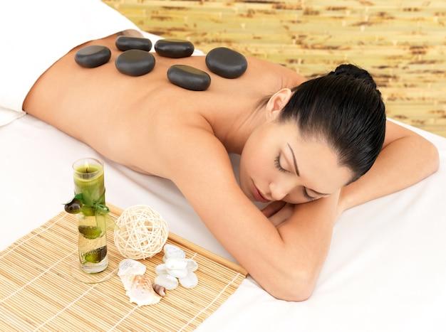 Steinmassage für junge frau im beauty spa salon. erholungstherapie.
