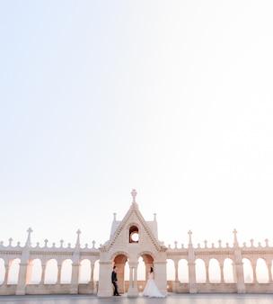 Steinmauer, blauer himmel und winzige braut und bräutigam, heiratskonzept am hellen sommertag
