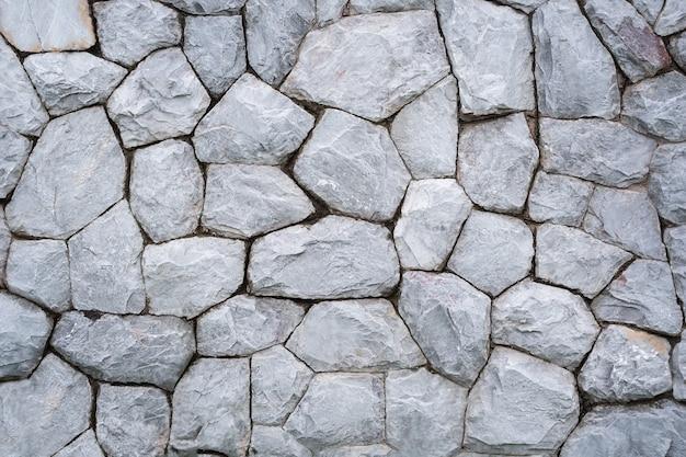 Steinmauer hintergrund. texturwand aus grauen runden steinen