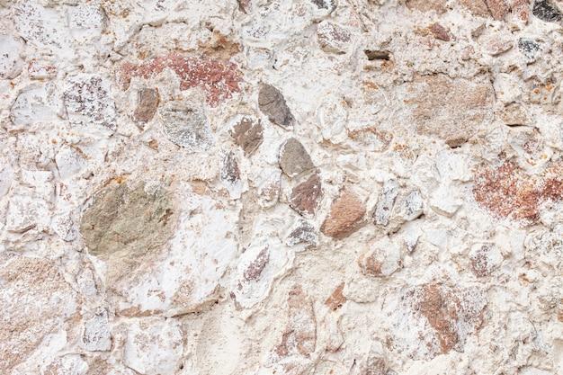 Steinmauer textur. mosaikfelsen dekorativer wandhintergrund. mauer aus alten steinen. dekorative verkleidung der außenwände des hauses.