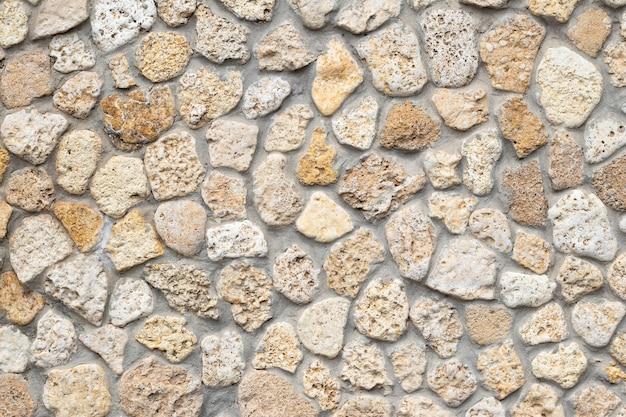 Steinmauerhintergrund, beige kopfsteinpflaster, abstrakte felsenstruktur, mineralischer bürgersteig, helle ziegeltapete, raues mauerwerk. grunge-boden, felsbrocken.