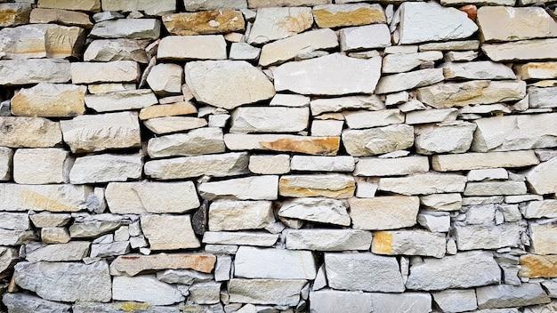 Steinmauertextur als hintergrund oder textur. muster graue farbe modernes design dekorative ungleichmäßige risse echte oberfläche.
