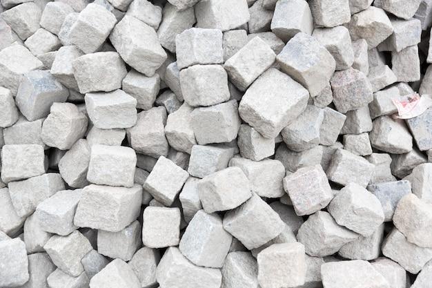 Steinpflastersteine zum verlegen der straße, die für bauarbeiten in einen haufen gegossen werden. nahaufnahme. foto in hoher qualität