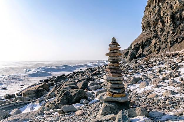 Steinpyramide im winter auf einem felsigen strand einer gefrorenen bucht, die mit schnee bedeckt wird