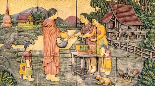 Steinschnitzen des anbietens des lebensmittels zu den buddhistischen mönchen auf tempelwand