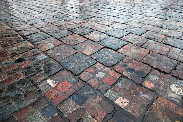 Steinstraße nach regen - fotografierte nahaufnahme nasse straße aus stein, nach dem regen,
