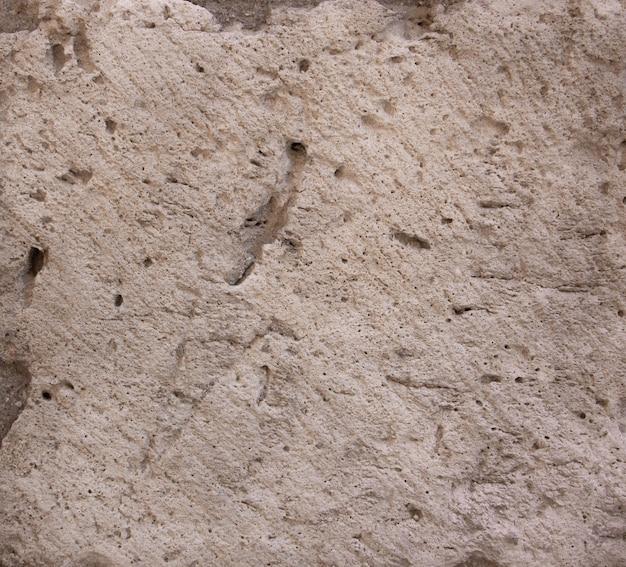 Steinstruktur in beige mit löchern. hintergrund.
