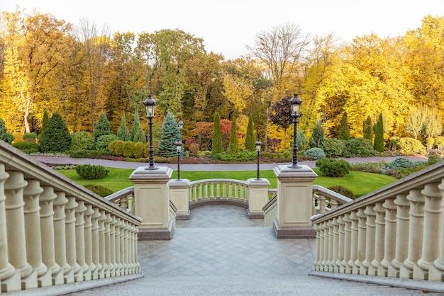 Steintreppe im mezhyhirya park, treppe mit laternen vor dem hintergrund der herbstbäume