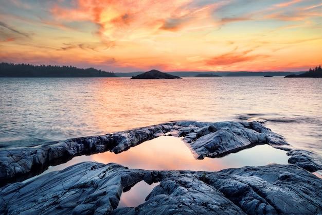 Steinufer des sees bei sonnenuntergang