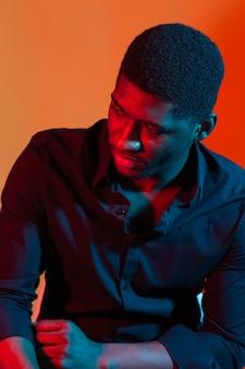 Stellen sie afroamerikaner stilvollen mann, der auf der blauen und roten neonlichtwand aufwirft.