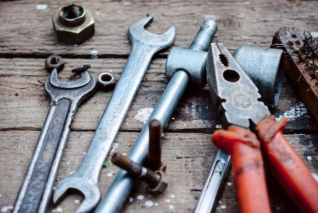 Stellen sie alte manuelle werkzeuge ein. verwitterte holzoberfläche liegen die alten, öligen schraubenschlüssel, zangen. fast verstreute alte rostige nüsse.