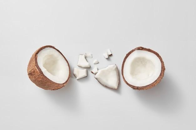 Stellen sie aus frisch brocken reifen natürlichen organischen exotischen kokosnussfrüchten auf einem hellgrauen hintergrund mit weichen schatten und kopierraum ein. veganes konzept. draufsicht.