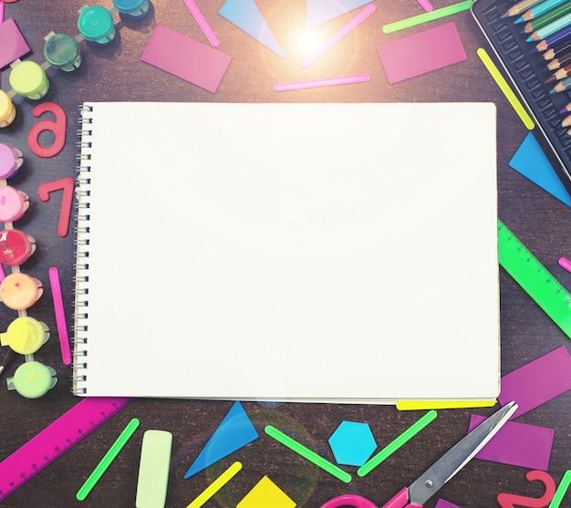 Stellen sie briefpapier für das schulnotizbuch ein, das auf dem tisch liegt. draufsichtkopienraum konzept zurück zu schule