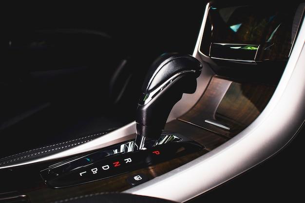 Stellen sie einen schalthebel in die p-position (parken) und das schaltpositionssymbol am automatikgetriebe in einem luxusauto.
