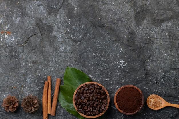 Stellen sie flach liegende kaffeebohnen in holzbecher auf grünes blatt, zucker in holzlöffel, kiefer auf schwarzen stein