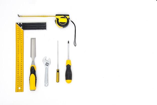 Stellen sie gelbe werkzeuge auf draufsicht des weißen hintergrundes ein. tischler arbeitstisch. tischler- und holzindustrie flach zu legen.