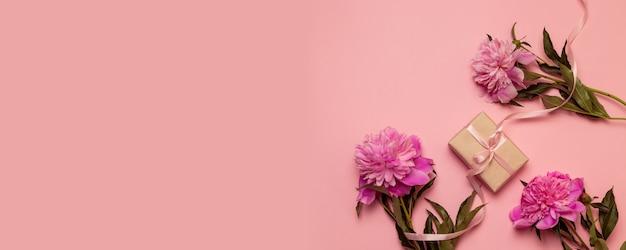 Stellen sie geschenkbox mit rosa pastellbogenband und pfingstrosenblumen auf rosa segeltuch her