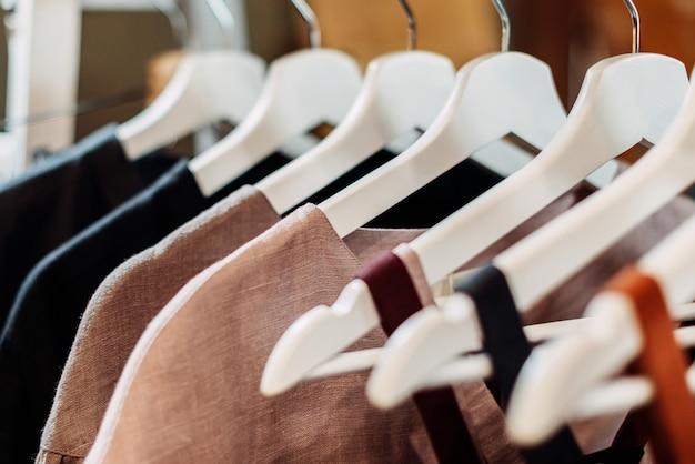 Stellen sie im laden vintage-leinenkleider her, die auf kleiderbügeln hängen.