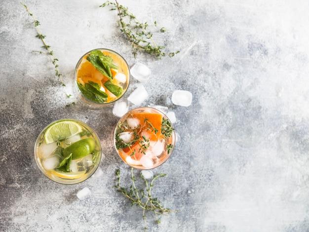 Stellen sie kalte getränke des sommers mit unterschiedlicher zitrusfrucht in den gläsern auf einem grauen hintergrund ein.