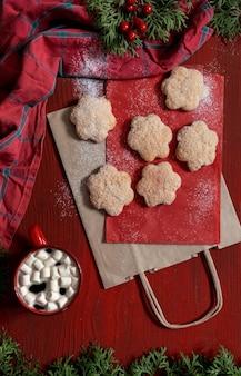 Stellen sie kekse auf roten holztisch mit roter tasse kaffee und einkaufstüten-lieferkonzept