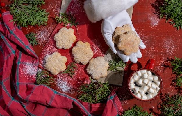 Stellen sie kekse auf roten holztisch mit roter tasse kaffee und hand des weihnachtsmanns, lieferkonzept.