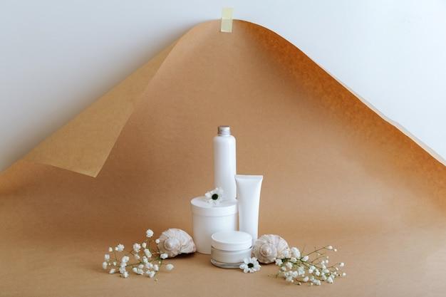 Stellen sie kosmetische hautpflegeprodukte der natürlichen schönheit mit blumenmuscheln auf beigebraunem hintergrund ein. weißes kit creme tube lotion kosmetische weibliche produkte für die körperbehandlung hautpflege kosmetisches modell.