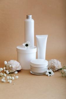 Stellen sie kosmetische hautpflegeprodukte der natürlichen schönheit mit blumenmuscheln auf beigem hintergrund ein. weibliche weiße kit-sahneglas-röhren-kosmetikprodukte für die körperbehandlung, hautpflege, kosmetisches modell.