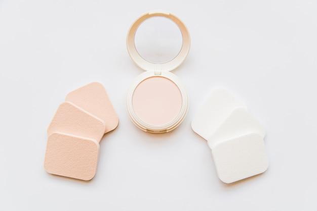 Stellen sie kosmetisches kompaktes make-uppulver mit schwämmen auf weißem hintergrund gegenüber