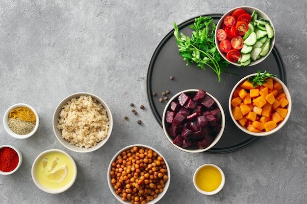 Stellen sie lebensmittel für das kochen von gesundem vegetarischem essen ein. gewürzte kichererbsen, gebackener kürbis und rote rüben, quinoa und gemüse draufsicht