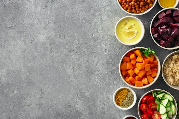 Stellen sie lebensmittel für das kochen von gesundem vegetarischem essen ein. gewürzte kichererbsen, gebackener kürbis und rote rüben, quinoa und gemüse.