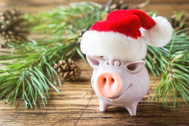 Stellen sie lustiges schwein in sankt hut auf einem holztisch mit niederlassungen der fichte dar.
