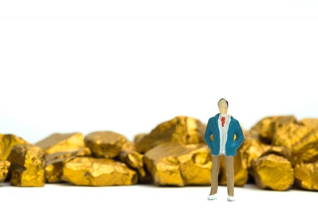 Stellen sie miniaturgeschäftsmann oder kleine leute mit stapel von goldnuggets oder von golderz auf weißem hintergrund dar