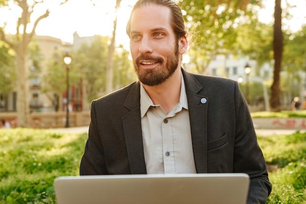 Stellen sie nahaufnahme des sachlichen gutaussehenden mannes mit gebundenem haar auf, der auf silbernem laptop arbeitet, während sie im stadtpark während des sonnigen tages ruhen