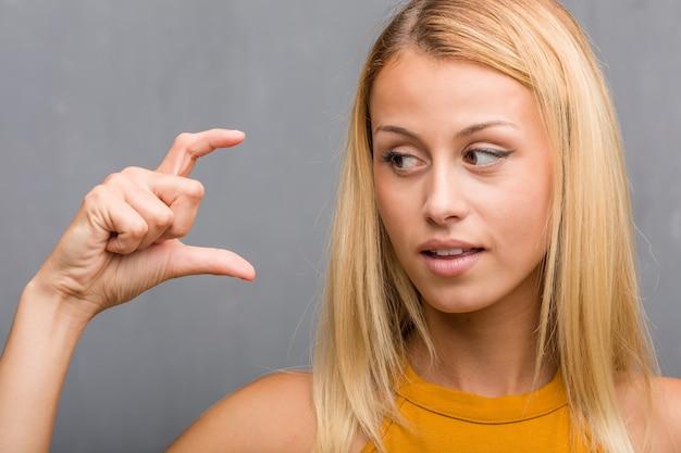 Stellen sie nahaufnahme, porträt einer natürlichen jungen blondine gegenüber, die etwas mit den händen hält, ein produkt zeigen, lächeln und nett, einen eingebildeten gegenstand anbietend