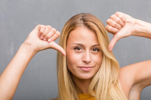Stellen sie nahaufnahme, porträt einer natürlichen jungen blondine gegenüber, stolz und überzeugt, finger zeigend, beispiel, konzept der zufriedenheit, arroganz und gesundheit zu folgen