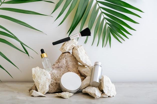 Stellen sie natürliche schönheit kosmetische hautpflegeprodukte make-up-pinsel mit palmblattpflanze auf steinsockel, steinhaufenausgleichssteine ein. serum tropfcreme butter hautpflege kosmetikmodell auf grauem hintergrund