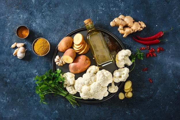 Stellen sie rohen bestandteilvorbereitung vegetarischen indischen teller aloo gobi ein