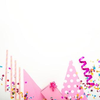 Stellen sie rosa geschenkbox mit dekorativen einzelteilen auf weißem hintergrund dar