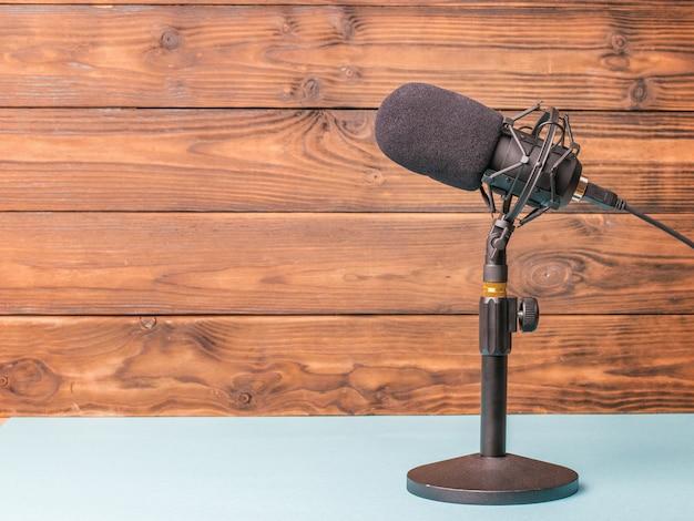 Stellen sie sich mit einem modernen mikrofon auf einen blauen tisch auf einer holzoberfläche