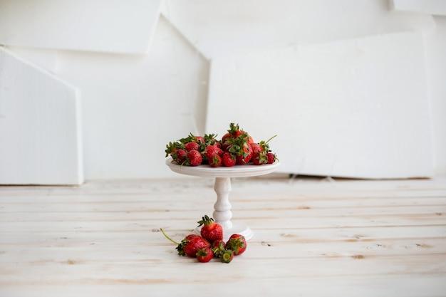 Stellen sie sich mit einem strauß erdbeeren an eine weiße wand mit platz für text