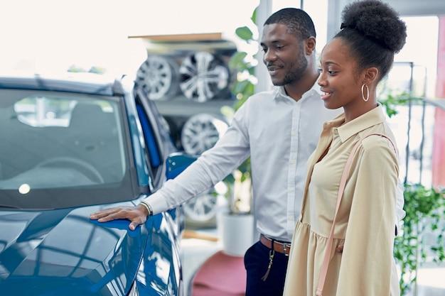Stellen sie sich uns auf der straße vor. porträt des glücklichen afroamerikanerpaares, das ein auto auscheckt