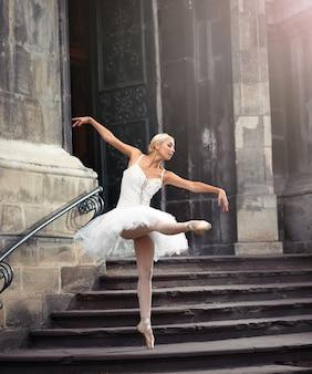 Stellen sie sich vor, sie tritt auf. ganzaufnahme einer talentierten ballerina, die in der nähe eines alten schlosses tanzt