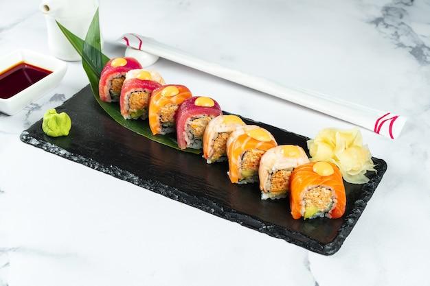 Stellen sie sushi-rollen ein, die auf einem bananenblatt auf einem schwarzen stein auf einem marmortisch mit stäbchen und sojasauce serviert werden. japanisches essen. lachs-thunfisch-garnelen-sushi. gesunde meeresfrüchte.