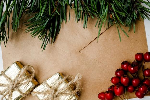Stellen sie umschlag mit einer niederlassung vom weihnachtsbaum, vom weißdorn und von den geschenken in handarbeit