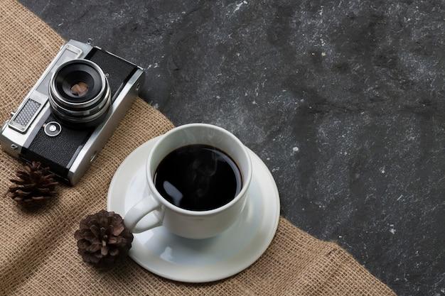 Stellen sie weißen schalenkaffee und alte kamera, die kiefer ein, die auf leinwand im schwarzen stein trocken ist