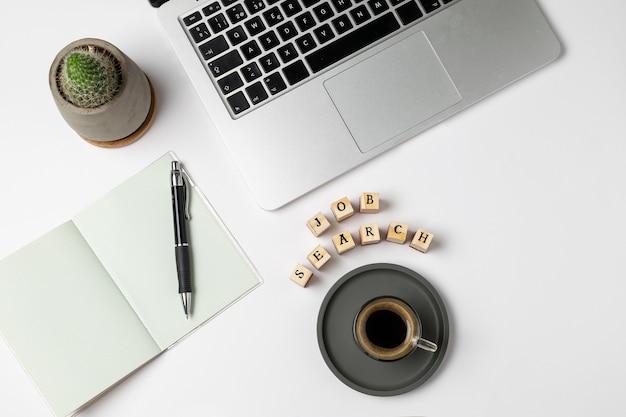 Stellenrecherchenwort auf stempeln, kaffeetasse, tastatur, stift, notizblock, arbeitslosigkeit auf grau
