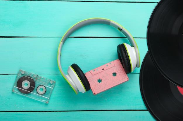 Stereo-kopfhörer mit audiokassette, schallplatten auf blauem holztisch